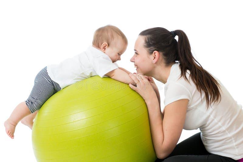 Jonge moeder en haar baby die yogaoefeningen op gymnastiek- die bal doen over wit worden geïsoleerd stock afbeeldingen