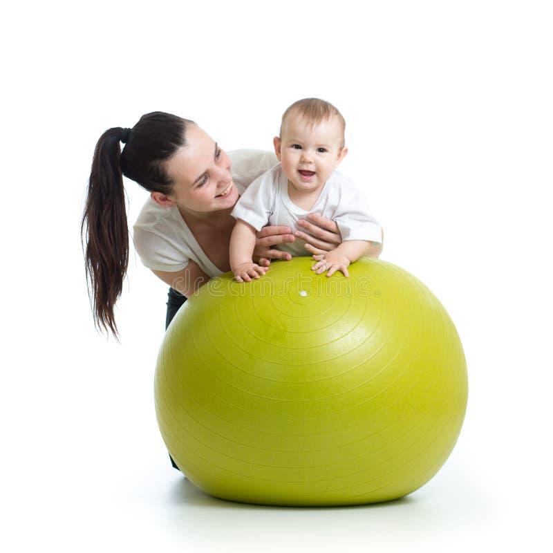 Jonge moeder en haar babykind die yogaoefeningen op gymnastiek- die bal doen over wit worden geïsoleerd stock fotografie