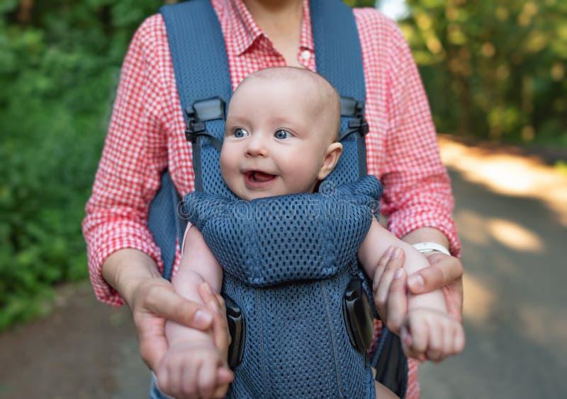 Jonge moeder en haar babymeisje in een babydrager royalty-vrije stock afbeeldingen