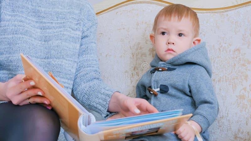 Jonge moeder en haar babyzoon die photobook kijken stock afbeeldingen