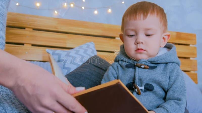 Jonge moeder en haar de lezingsboek van de babyzoon thuis royalty-vrije stock foto's