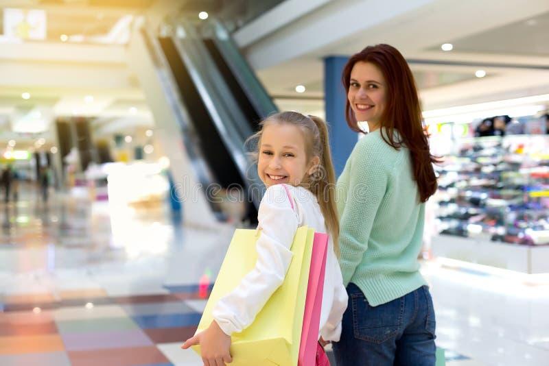 Jonge moeder en haar dochter doen die samen winkelen stock foto's
