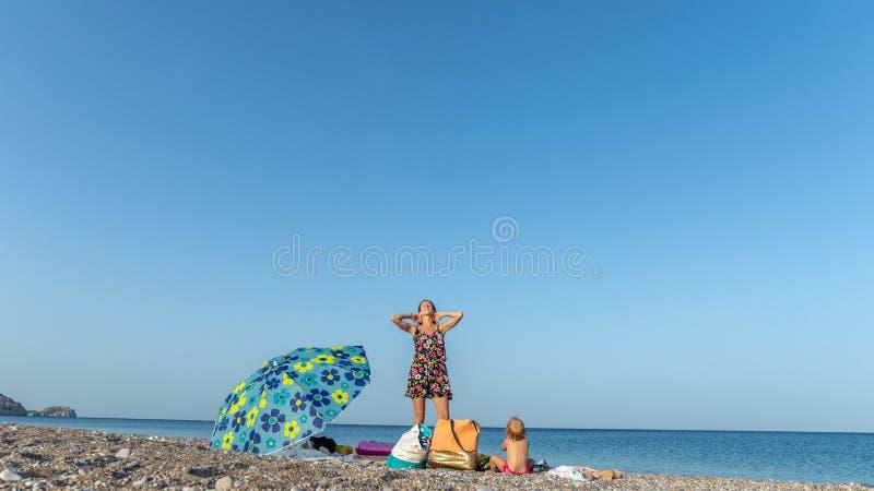 Jonge moeder en haar dochter op een kiezelsteenstrand in Griekenland royalty-vrije stock foto