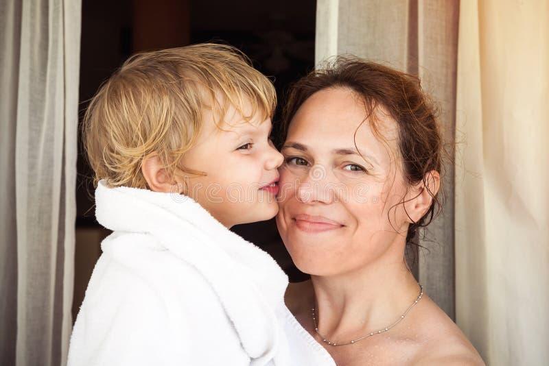Jonge moeder en haar leuk blond babymeisje in handdoek stock foto