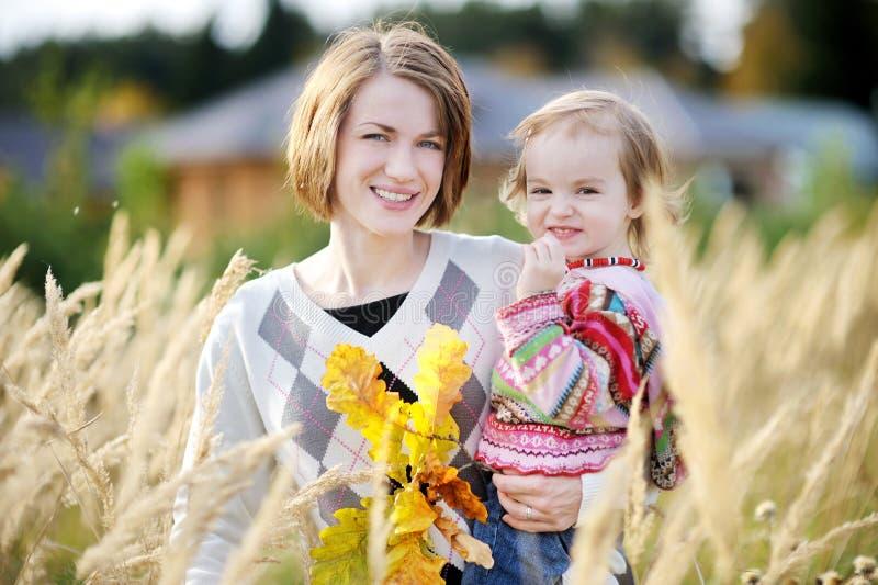 Jonge moeder en haar peutermeisje in de herfst royalty-vrije stock afbeelding