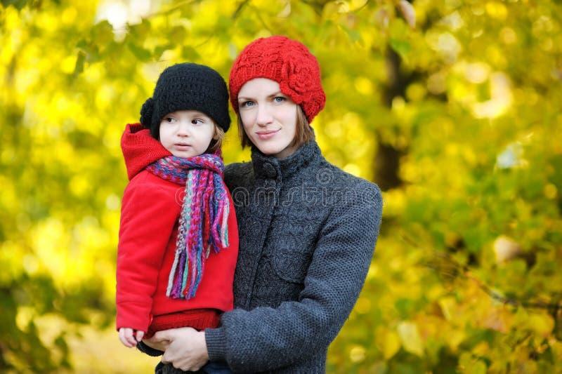Jonge moeder en haar peutermeisje in de herfst royalty-vrije stock afbeeldingen