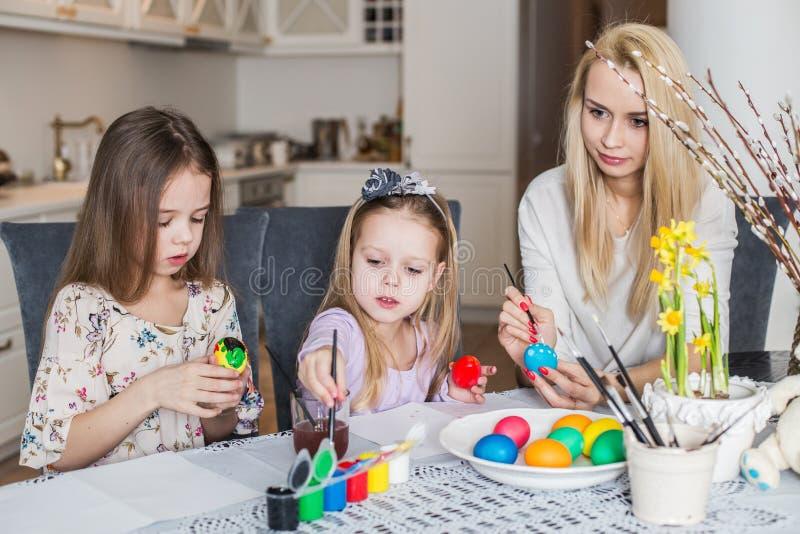 Jonge moeder en haar twee dochters die paaseieren schilderen stock afbeelding