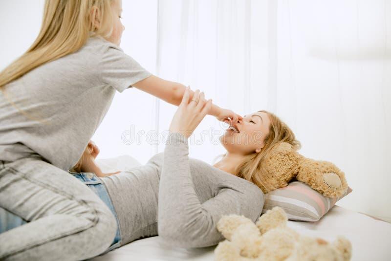 Jonge moeder en haar weinig dochter die en op bed koesteren kussen royalty-vrije stock afbeeldingen