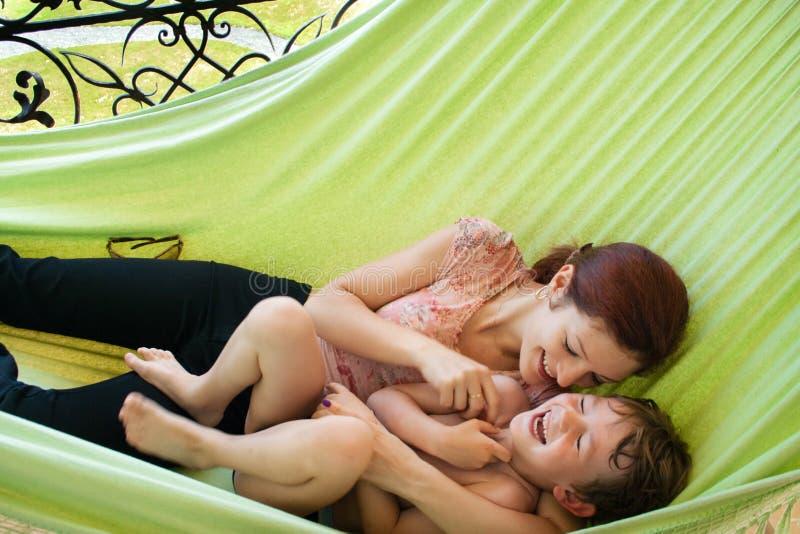 Jonge moeder en haar weinig zoon die in een hangmat ontspannen stock foto's