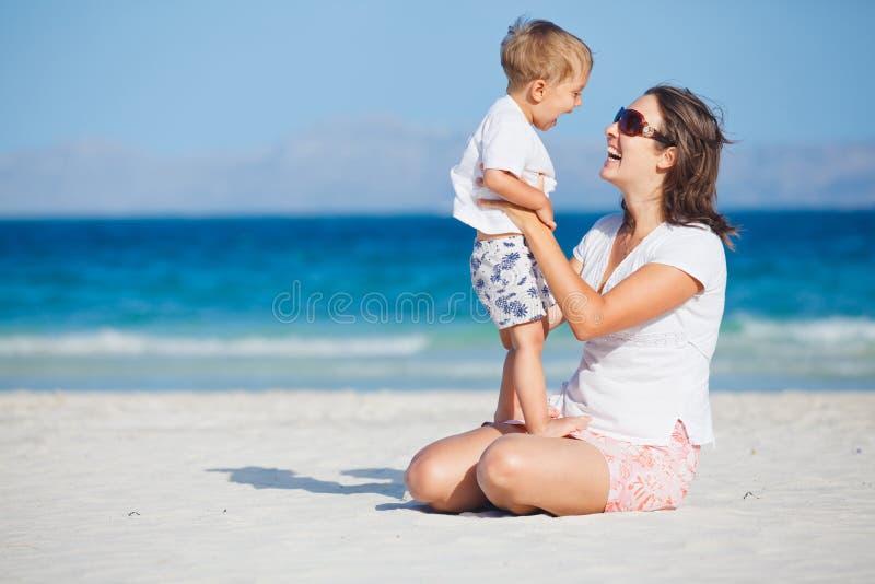 Jonge moeder en haar zoon die bij strand spelen royalty-vrije stock afbeeldingen