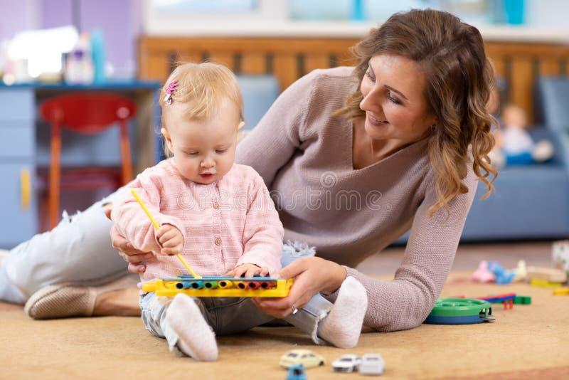 Jonge moeder en het leuke baby spelen op vloer thuis Mamma die haar meisje onderwijzen hoe te op stuk speelgoed metallophone te s stock foto's