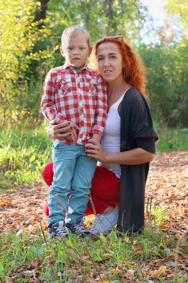 Jonge moeder en knap weinig zoon in de herfstpark royalty-vrije stock afbeeldingen