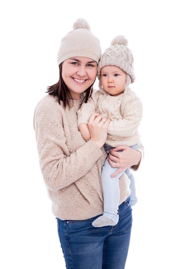 Jonge moeder en leuk babymeisje in de winter wollen sweaters en hoeden die op wit worden geïsoleerd stock fotografie