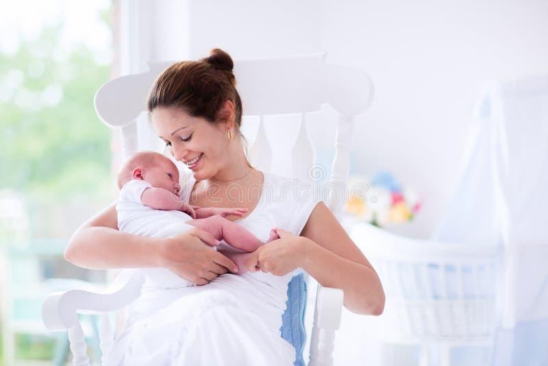 Jonge moeder en pasgeboren baby in witte slaapkamer stock afbeelding