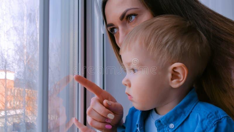 Jonge moeder en peinzend weinig jongen die door venster kijken royalty-vrije stock foto