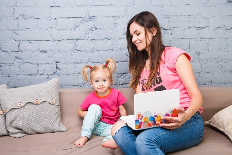 Jonge moeder en twee éénjarigenmeisje met blonde haarzitting op de laag en het gebruiken van laptop Zij zijn gekleed in heldere r royalty-vrije stock afbeelding