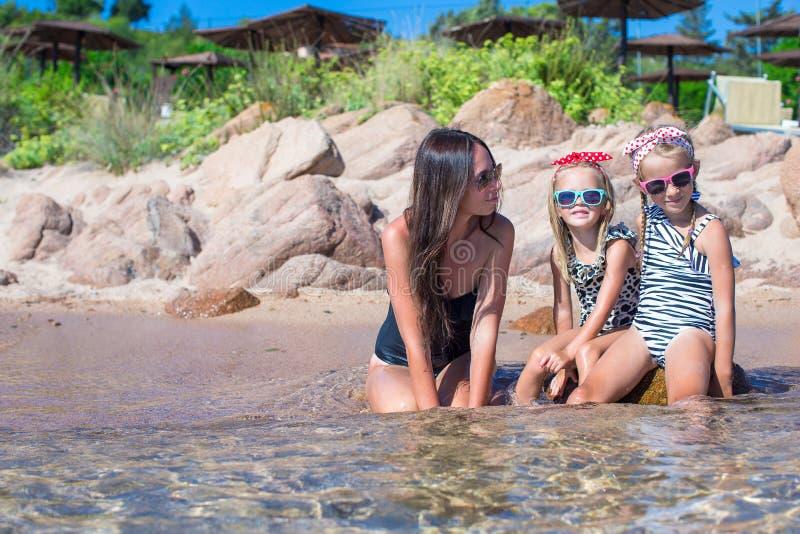 Jonge moeder en twee haar jonge geitjes bij exotisch strand stock foto