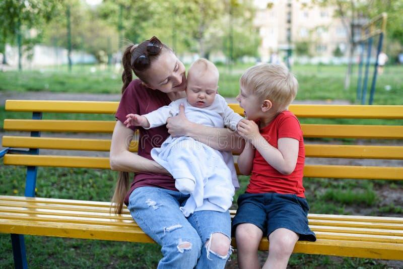 Jonge moeder en twee kinderen op een bank in het park Baby en het blonde oudere broer spelen De warme dag van de lente stock afbeelding