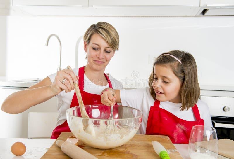 Jonge moeder en weinig zoete dochter in kokschort die samen het bakken koken bij moderne huiskeuken royalty-vrije stock foto's