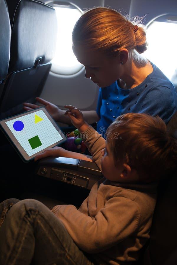 Jonge moeder en zoon die op een vliegtuig reizen royalty-vrije stock afbeeldingen