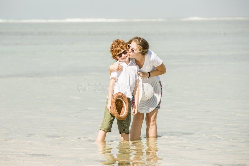 Jonge moeder en zoon die pret op het strand hebben stock fotografie