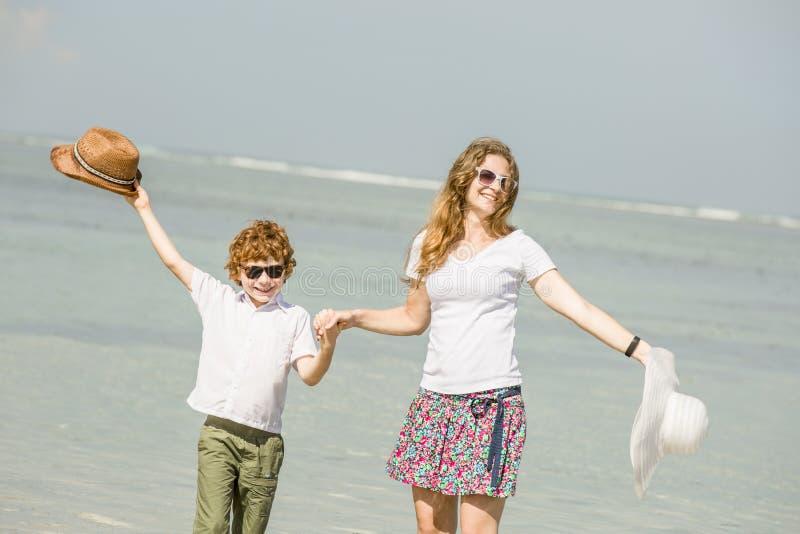 Jonge moeder en zoon die pret op het strand hebben royalty-vrije stock foto