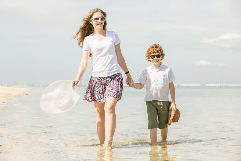 Jonge moeder en zoon die pret op het strand hebben royalty-vrije stock afbeelding