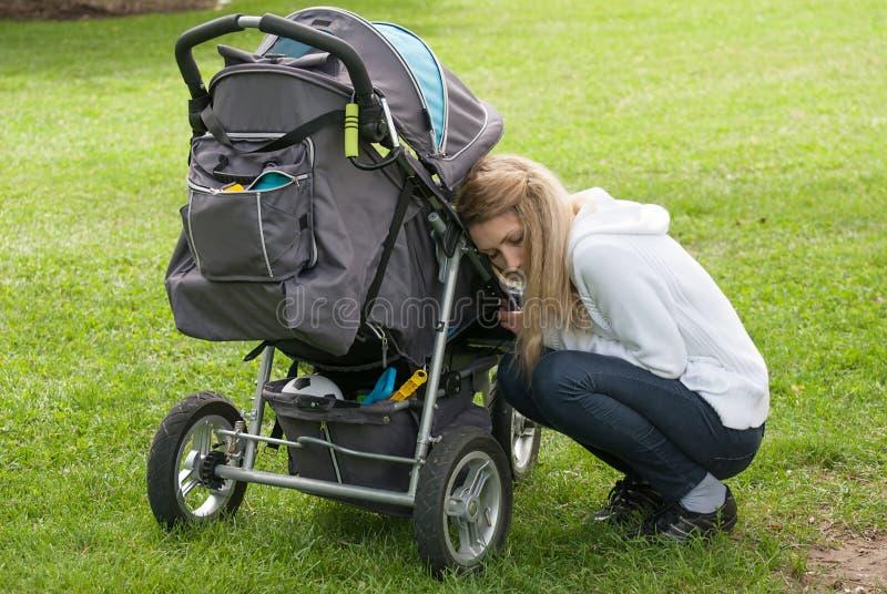 Jonge moeder en zoon in wandelwagen stock afbeelding