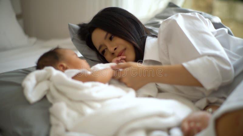Jonge moeder kijkt naar een kleine baby met een houding van geluk royalty-vrije stock afbeeldingen