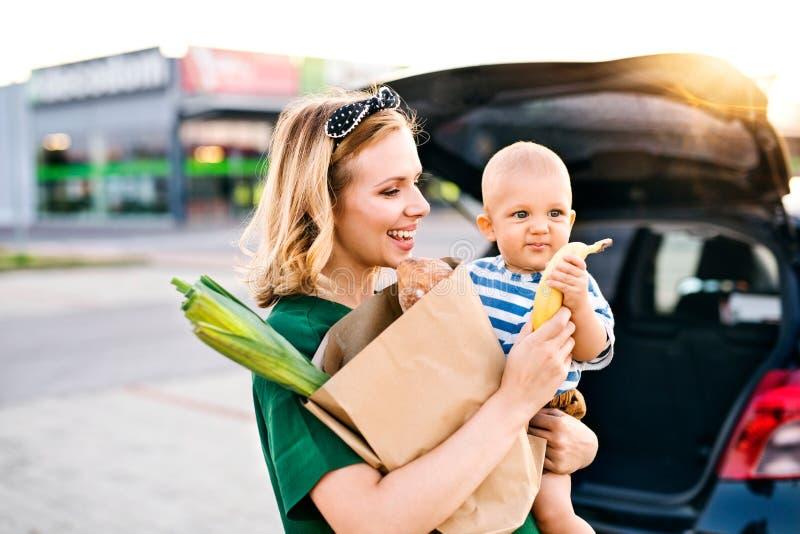 Jonge moeder met babyjongen voor een supermarkt stock afbeelding