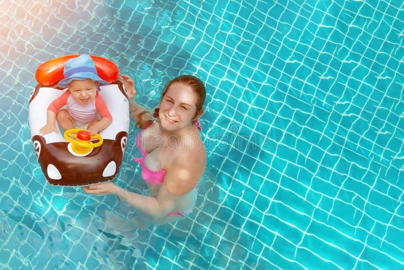 Jonge moeder met babymeisje die van pool in water genieten Exemplaarruimte bij het recht stock foto's