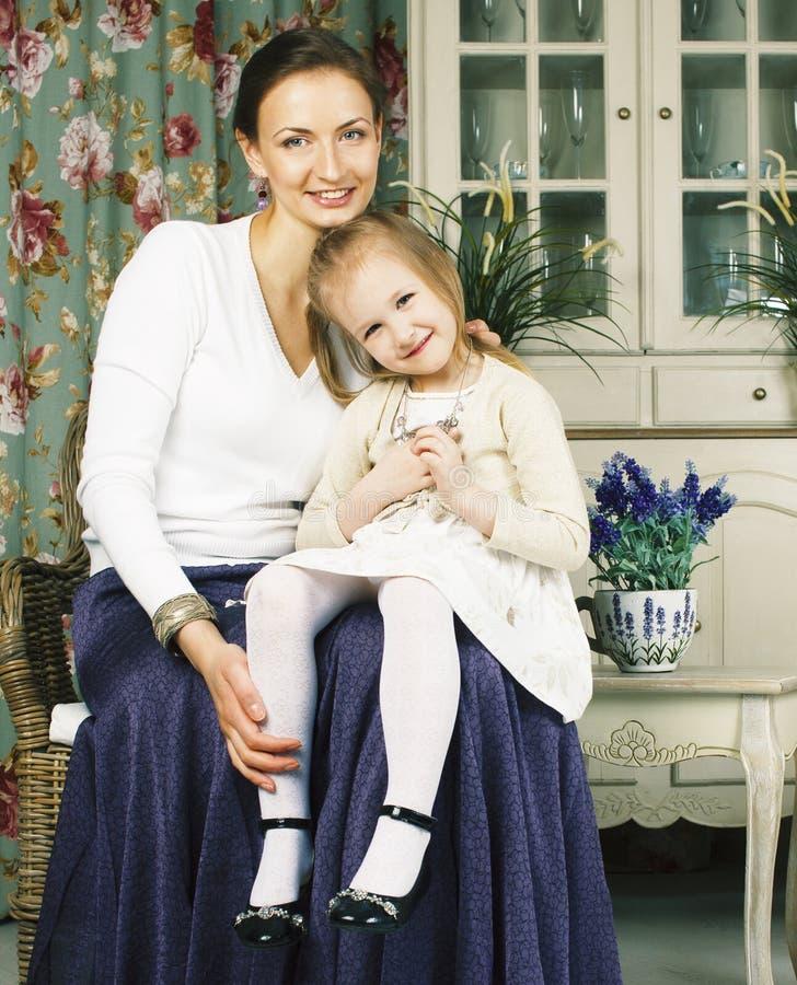 Jonge moeder met dochter bij de binnenlandse wijnoogst van het luxehuis stock afbeelding