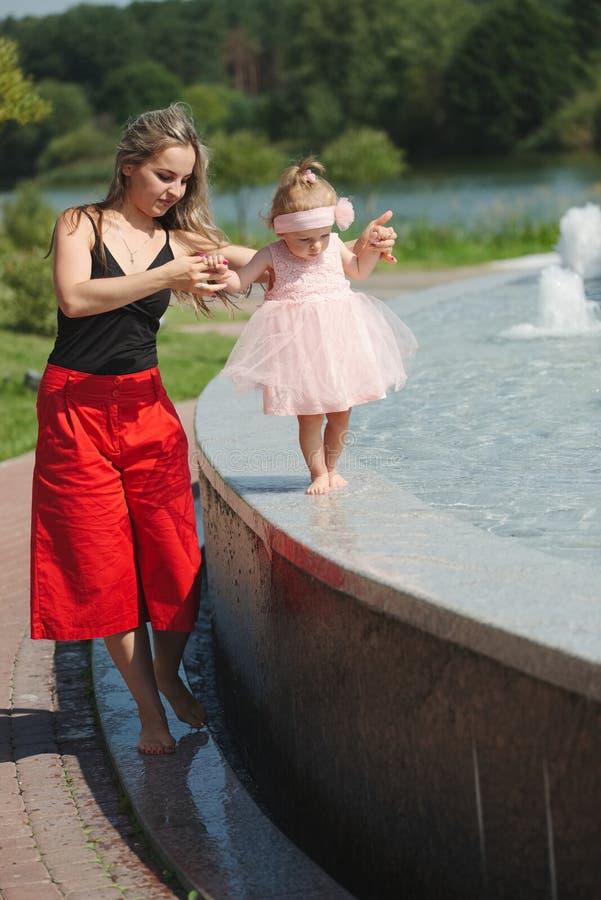 Jonge moeder met dochter bij fontein stock foto