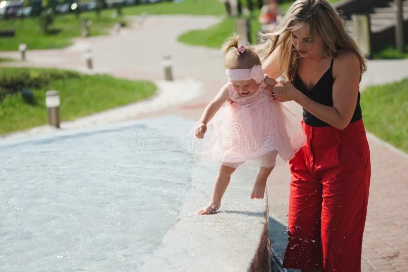 Jonge moeder met dochter bij fontein stock afbeeldingen