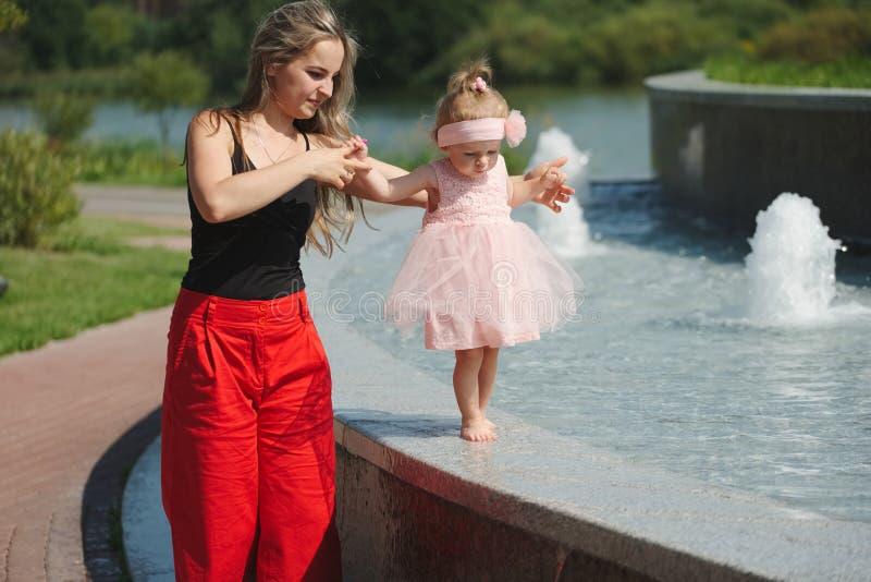 Jonge moeder met dochter bij fontein royalty-vrije stock afbeelding