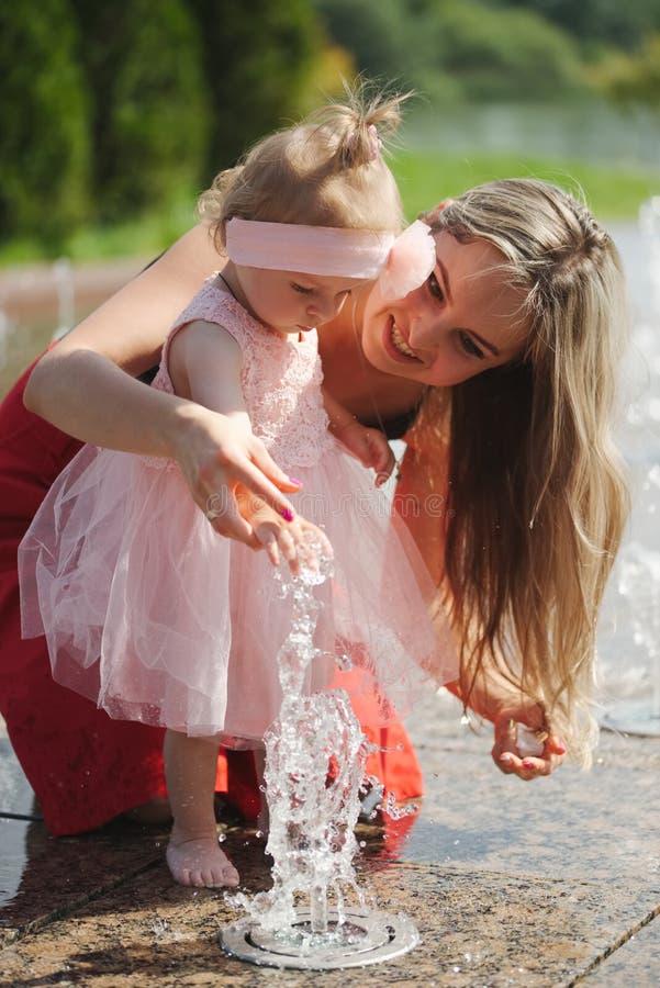 Jonge moeder met dochter bij fontein stock foto's