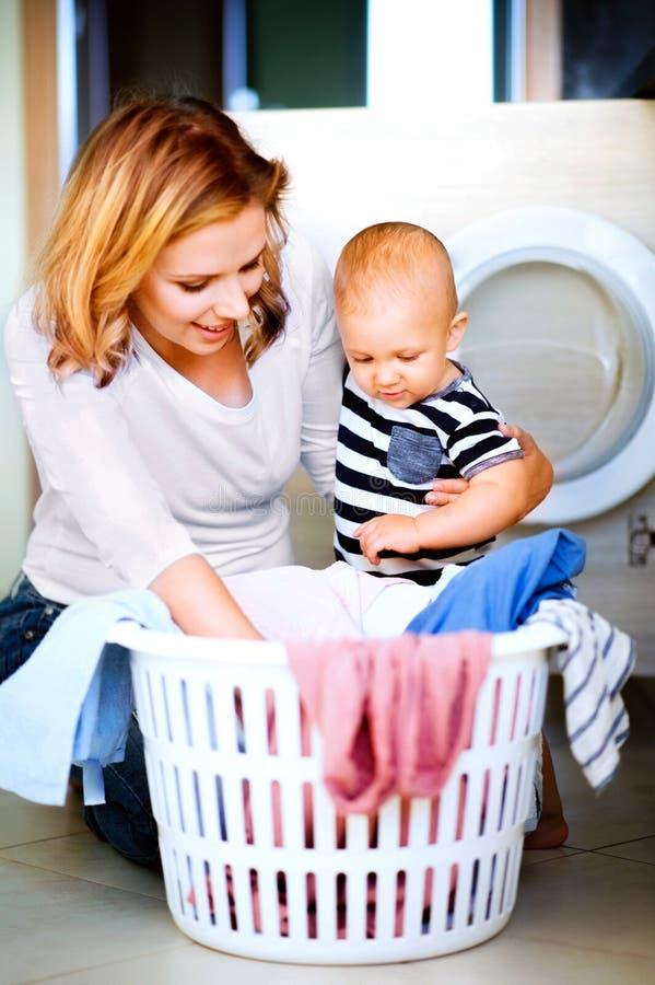 Jonge moeder met een babyjongen die huishoudelijk werk doen stock foto
