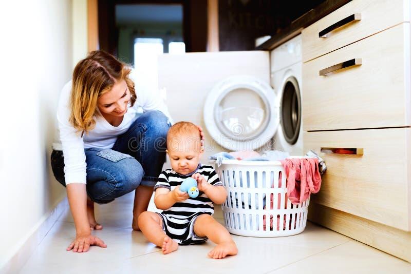 Jonge moeder met een babyjongen die huishoudelijk werk doen stock afbeelding