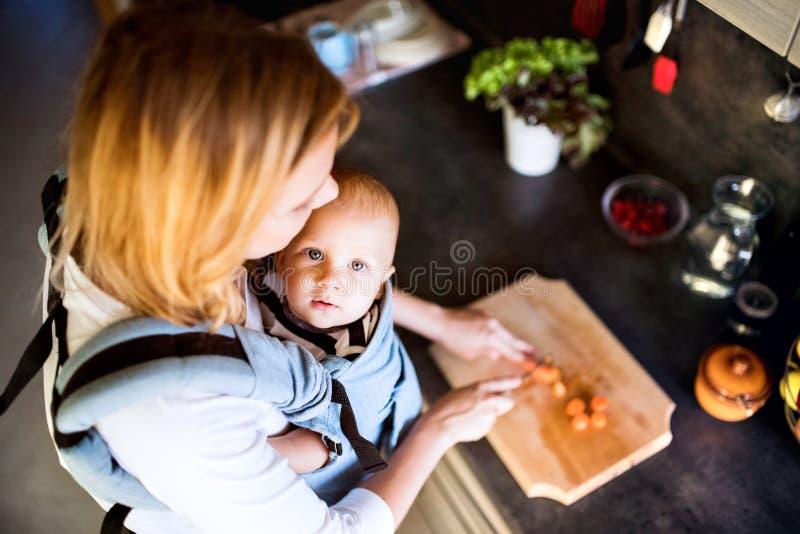 Jonge moeder met een babyjongen die huishoudelijk werk doen royalty-vrije stock foto