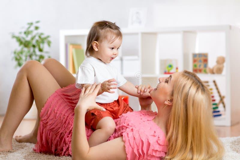 Jonge moeder met haar baby die prettijdverdrijf hebben royalty-vrije stock foto's