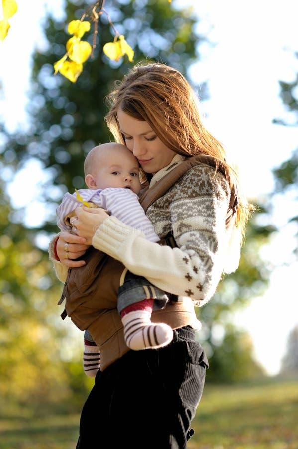 Jonge moeder met haar baby in een carrier stock fotografie