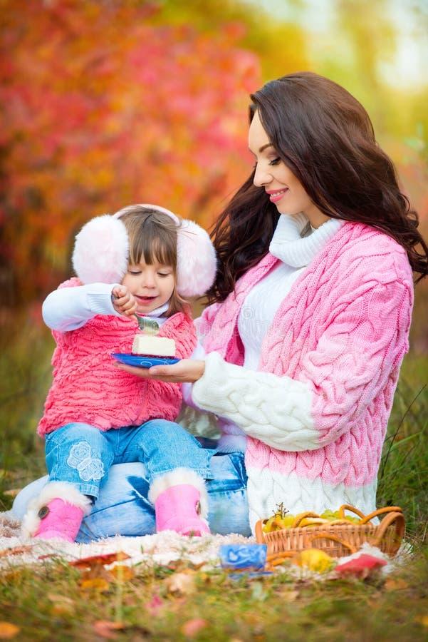 Jonge moeder met haar dochter bij een picknick in de parkherfst stock afbeelding