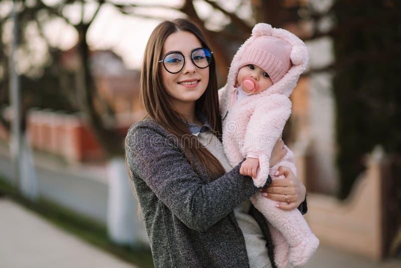 Jonge moeder met haar weinig baby De baby van de mammagreep op handen Gelukkige Familie stock fotografie