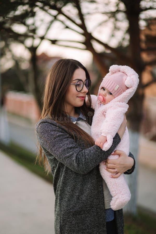 Jonge moeder met haar weinig baby De baby van de mammagreep op handen Gelukkige Familie stock afbeelding