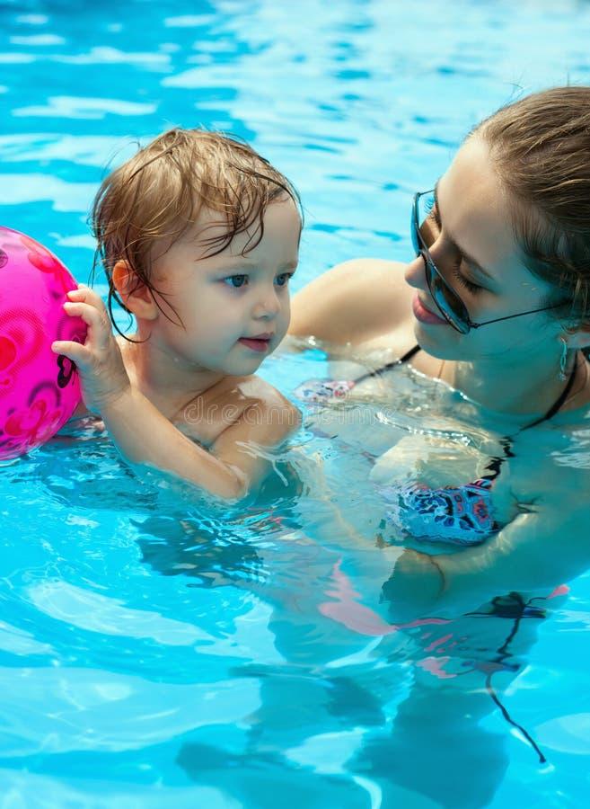 Jonge moeder met haar weinig dochter in de pool royalty-vrije stock afbeelding