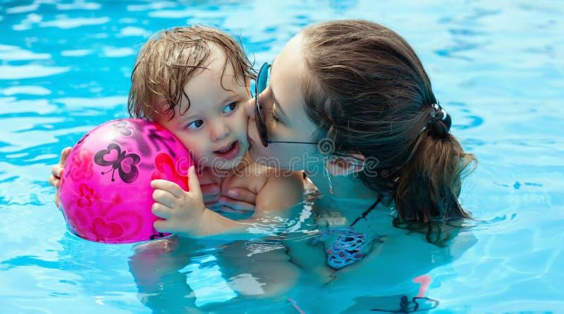 Jonge moeder met haar weinig dochter in de pool stock foto's