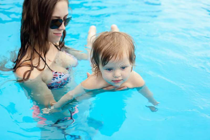 Jonge moeder met haar weinig dochter in de pool royalty-vrije stock foto