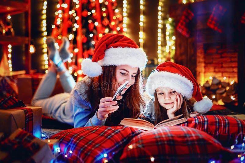Jonge moeder met haar weinig dochter die een boek lezen terwijl het zitten onder verfraaide Kerstboom op de vloer royalty-vrije stock foto