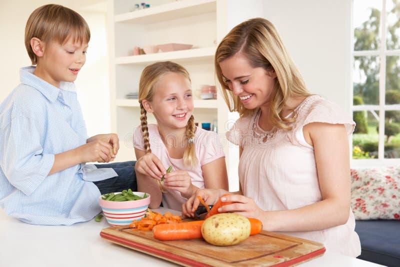 Jonge moeder met kinderen die groenten pellen royalty-vrije stock foto