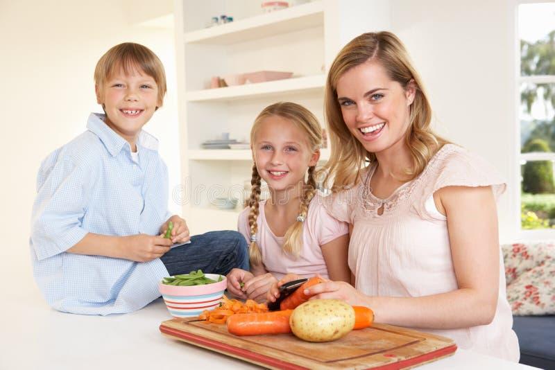 Jonge moeder met kinderen die groenten pellen stock afbeeldingen